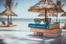 Photo d'une paire de lunettes posée sur une pile de livre, avec une plage et des parasols en arrière plan